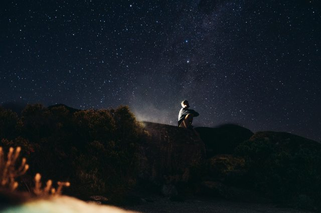 man-in-white-shirt-sitting-on-rock-during-night-time-3483524